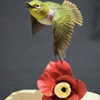 門永哲郎「鳥媒花」2020年、h20×w17×d21 cm、朴、桜(台)、黒檀(台/影)、椿材(メジロ、椿)、琥珀(メジロの目)、もちの木(目の回りの白い羽)、油彩で彩色_1